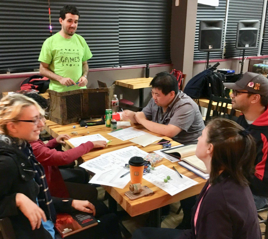 a group of people seated around a table laid out with papers, pencils, and multisided dice. One person stands at the head of the table leading a game.